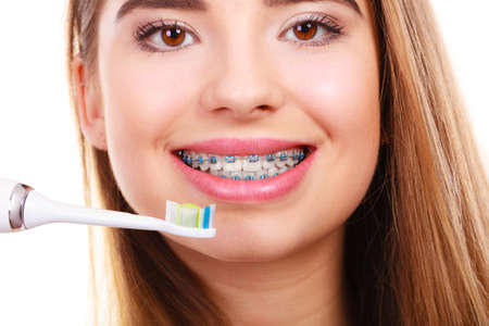 Dentist and orthodontist concept. Young woman cleaning and brushing teeth with blue braces using toothbrush Stock Photo