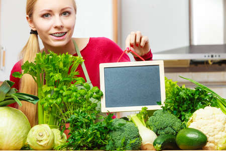 Young woman in kitchen having many green vegetables about to cook something healthy and vegetarian, holding blank black board for copyspace Stock Photo