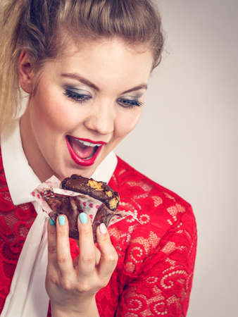 Sweet food sugar make us happy. Attractive blonde woman holds yummy chocolate cupcake in hand, open mouth, craving for cake.