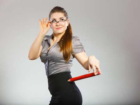 Teacher looking elegant woman wearing dark tight skirt, shirt and eyeglasses holding big oversized pencil Stock Photo