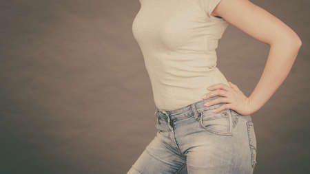 Woman wearing tight slim jeans and white tshirt, showing her great body curves. Well-fitting pants