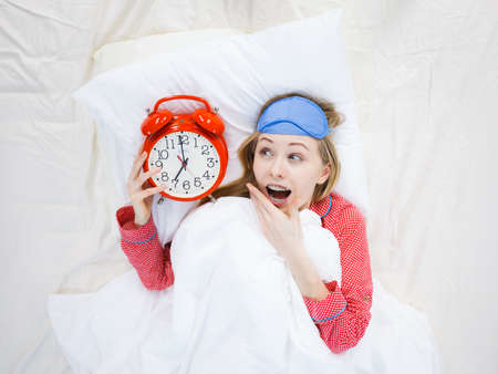 Shocked young woman being late wearing cute pink pajamas holding big red old fashioned clock showing time. 写真素材