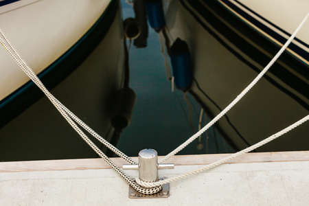 Jetty objects concept. New metal steel harbor marina bolts with ship and boats ropes. Stock Photo