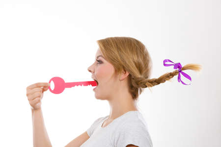 Language barrier concept. Teenage blonde girl with braid hair biting big pink key Stock fotó - 91365717