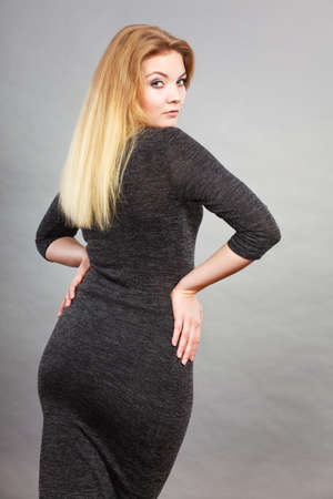 Woman wearing tight black dress showing her feminine body shape, back view.