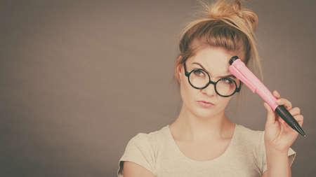 Student looking woman wearing nerdy eyeglasses holding big oversized pencil thinking about something. Stock Photo