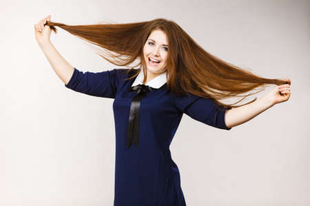 Happy positive woman brushing long brown hair presenting her healthy hairdo. Haircare concept. Studio shot on grey backgorund.