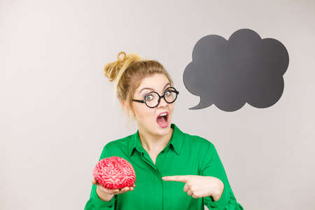 Business woman wearing green jacket and eyeglasses being rude and mad solution holding fake brain, black thinking or speech bubble next to her. Фото со стока