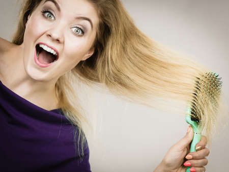 Happy woman combing her hair with brush. Young smiling female with natural blond straight long hairs, studio shot on grey