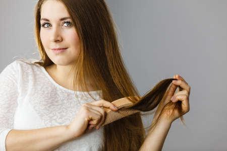 ヘアケアと朝のヘアスタイリングのコンセプト。彼女の長い暗い茶色の髪をブラッシング幸せな女性