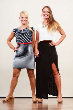 Fashionable style, clothes concept. Woman wearing white top and long black shirt showing her leg standing next to older female with short striped dress