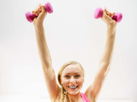 Teenage young woman working out at home with small light dumbbells. Training at home, being fit and healthy. Shot from down