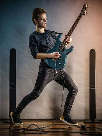 Young bearded man with electric guitar. Adult person in full length is holding instrument and playing. Hobby, music concept, on grey