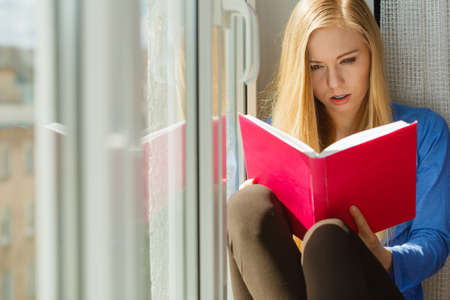 Young woman sitting on windowsill reading interesting book, having emotional face expression.