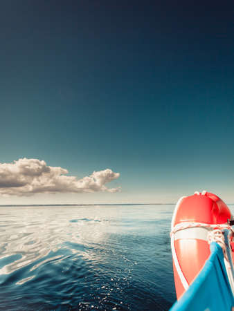 Water traveling, adventure concept. Sea view from yacht, lifebuoy close up, calm water, sunny weather, sky with many clouds. Zdjęcie Seryjne