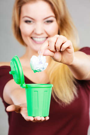 Cleaning, Woman putting paper into tiny trash can basket showing how to deal with rubbish