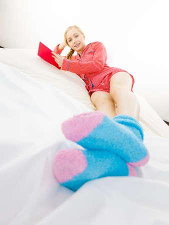 Meisje liggend in bed lezen boek. Jonge blonde vrouw met rode gestippelde pyjama blauwe warme sokken die thuis op matras ontspannen. Stockfoto - 92263697