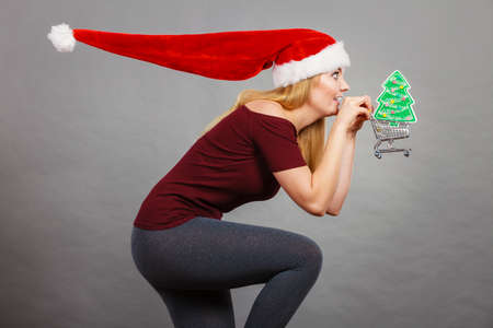Xmas, seasonal sales, winter celebration concept. Happy woman wearing Santa Claus helper hat holding shopping basket cart with little christmas tree inside running for sale.