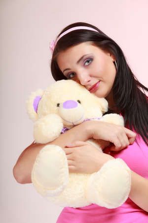 Portrait of childish young woman with headband holding toy. Infantile girl hugging teddy bear on pink. Longing for childhood. Studio shot. Stock Photo