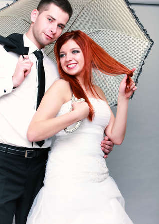 Wedding day. Portrait of happy married couple red haired blue eyed bride and groom with umbrella studio shot on gray background Stock Photo