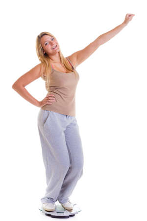 Woman plus size large happy girl with weight scale celebrating weightloss progress after diet victory, she lost some weight. Healthy lifestyles concept
