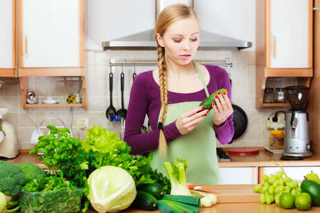 Woman young housewife in kitchen with many green leafy vegetables, fresh garden produce organically grown on counter. Healthy eating, cooking, vegetarian food, dieting and people concept.