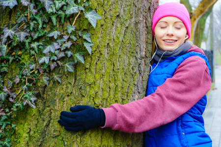 Woman wearing sportswear giving hug embracing tree trunk being in love with nature.
