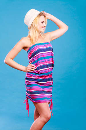 Summer trendy fashionable outfit ideas concept. Blonde woman wearing short colorful striped strapless dress and white sun hat