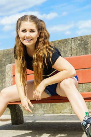 Happy joyful young woman wearing roller skates relaxing after long ride. Female being sporty having fun during summer time near sea.