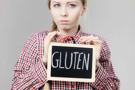 Angry young woman with braided hair holding small black board with gluten sign. Bakery and bread allergy problem.