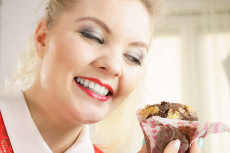 Sweet food sugar make us happy. Attractive blonde woman holds yummy chocolate cupcake in hand, craving for cake. Stock Photo