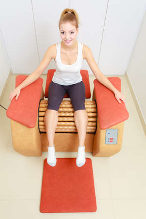 Skincare, bodycare, wellness concept. Woman getting rid of buttocks cellulite on big roll machine. Healthy massage treatment in spa