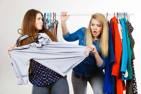 2人の面白い女性は、衣類の一部について買い物中にお互いに議論しています。セールス・マッドネス
