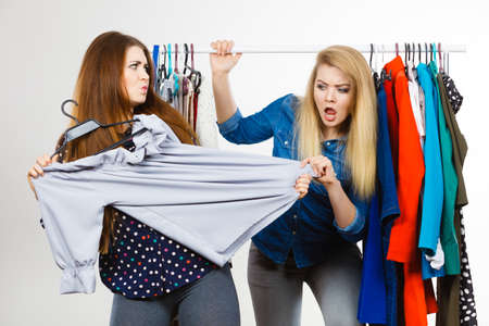 Two funny women arguing with each other during shopping about piece of clothing. Sales madness Foto de archivo