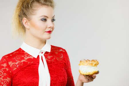 Concept de nourriture et de bonheur sucré. Femme tenant le délicieux gâteau choux à la crème fouettée.