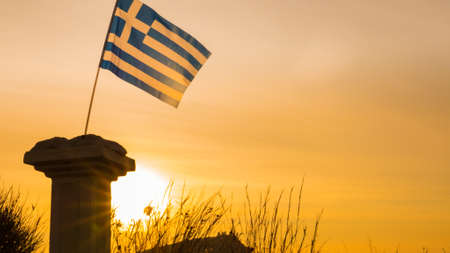 Greece Cape Sounion. Single greek column on sea shore and flag at sunrise, temple of Poseidon in the background,