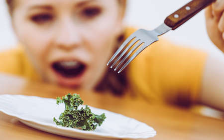 Shocked young blonde woman dealing with anorexia nervosa or builimia having small green vegetable on plate. Dieting problems, eating disorder.
