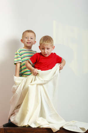 Childhood, relationship between brothers concept. Two little boys siblings playing together with towels and having fun.