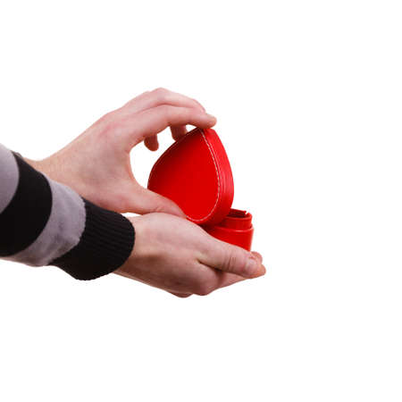 Holiday valentine day proposing concept. Man holding red heart shaped gift box in hand isolated 写真素材