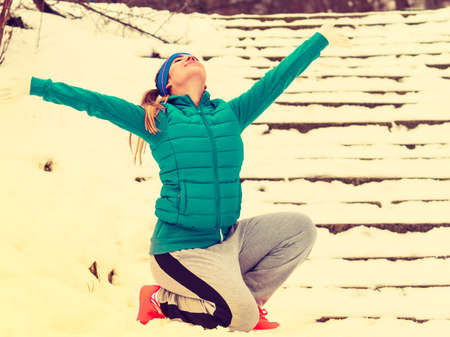 Outdoor sport exercising, sporty outfit ideas. Woman wearing warm sportswear training exercising outside during winter time, having fun.