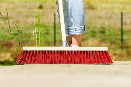 Unrecognizable female person using big broom to clean up backyard patio Stock Photo