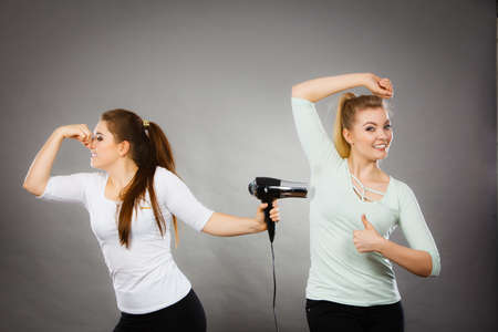 Woman drying her female friend wet armpit using hair dryer. Getting rid of sweat and bad smell, hyperhidrosis.