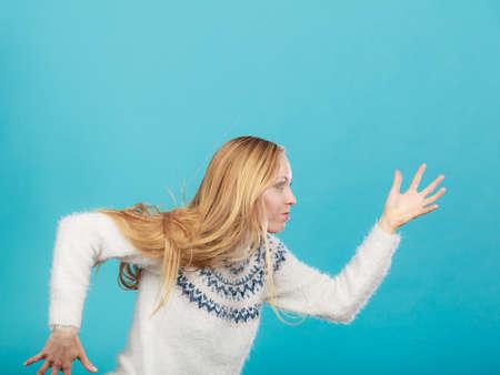 Weglopen van iets concept. Vrouw met lang blond haar uitgevoerd. Studio die op blauwe achtergrond is ontsproten. Stockfoto - 93139191