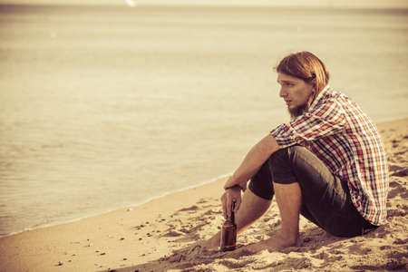 Man depressed with wine bottle sitting on beach outdoor. People abuse and alcoholism problems Stock Photo