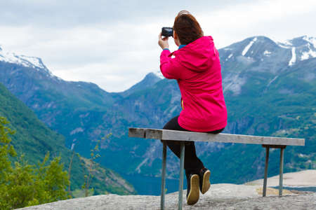 Tourism adventure and travel. Female tourist hiker sitting on bench in stone mountains taking photo with camera, looking at scenic view, Norway Scandinavia. Standard-Bild