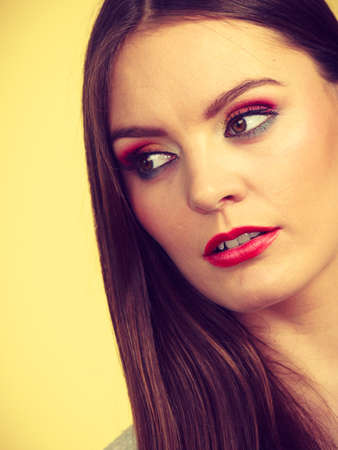 Pensive attractive brunette woman with full makeup having serious, thinking face expression. Stock Photo