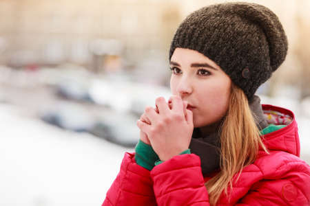 Woman during winter snowy day warming up her cold hands. Weather conditions, forecasting concept.