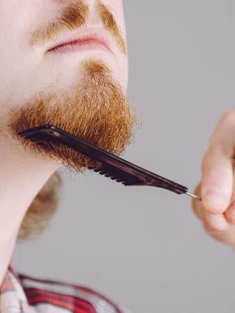 生姜オタクの男は、顔の髪の世話を櫛を使用して彼のひげをブラッシング。