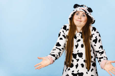 Teenage girl in funny nightclothes, pajamas cartoon style making silly face, shrugging woman in doubt doing shrug, confused girl gesturing do not know sign, studio shot on blue. Stock Photo