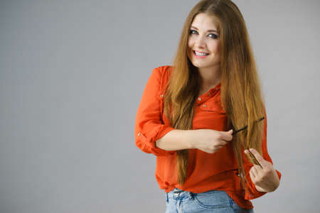 Happy funny teenage woman combing her long brown hair showing beautiful hairdo and non split ends.